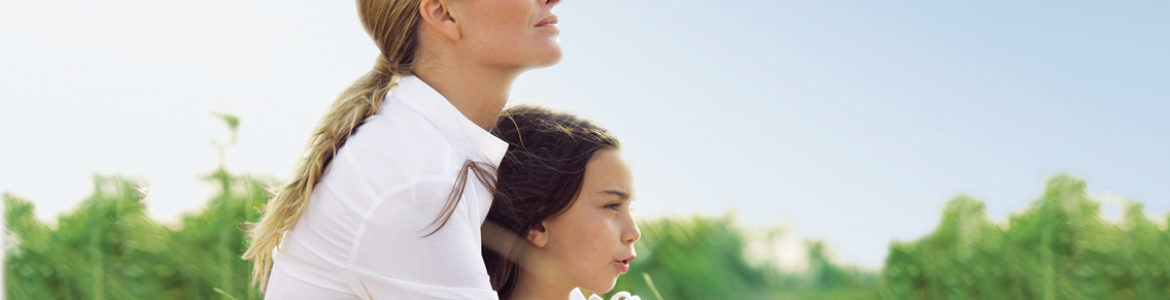 Mother and daughter (6-8) sitting on grassy dunes, profile